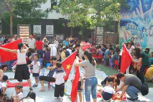 """本新闻发表于:2009-10-14 12:33 点击: 孩子,为祖国祝福吧 ——金色童年幼儿园举行亲子制作国旗活动 在国庆节即将来临之际,2009年9月30日江南村金色童年幼儿园开展了""""祖国妈妈生日快乐,祖国妈妈我们爱你""""的庆祝活动。 随着肖园长一声""""升旗仪式现在开始。""""活动拉开了序幕。小小升旗手们随着高昂的音乐,高举着五星红旗神气地走入会场,孩子们感受着这个庄严的时刻。 升旗仪式结束后,就是亲子制作国旗活动,活动中,小朋友在家长的帮"""
