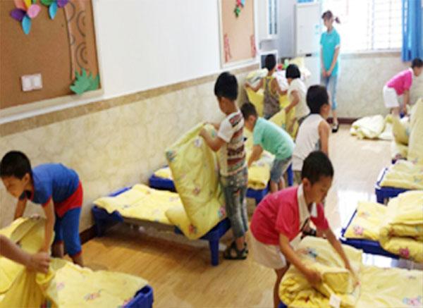 """为了更好的培养幼儿自我服务意识,提高幼儿自我服务能力,2014年6月6日,北京红缨东湖国际幼儿园苗苗班、朵朵班进行了一场别开生面的叠被子比赛。上午10点10分,孩子们个个信心十足,勇敢挑战。随着一声令响,比赛开始了。小朋友们灵巧的小手就动起来了:展开、铺平、折叠,动作流畅,一气呵成,把被子叠得又快又整齐。经过紧张比赛,评出了7名""""叠被子小能手""""。 叠被子比赛,使幼儿的生活自理能力和动手能力得到锻炼与提升,让每一个参与的幼儿体验到了我参与、我快乐。我能行。"""
